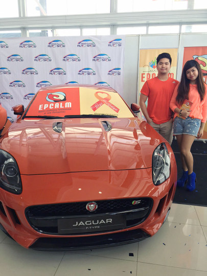 Epcalm volunteers pose beside the Jaguar F-Type at the MIAS